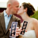 couple kissing and holding wedding favor photographs